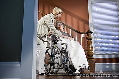Nurse helping elderly woman in wheelchair at home