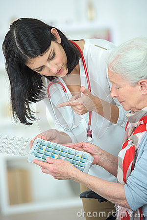 Free Nurse Helping Old Woman With Pill Box Stock Images - 82830904