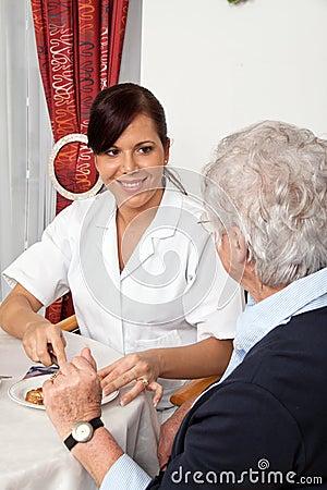 Nurse helping senior at breakfast