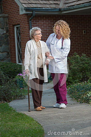 Nurse Helping Senior Walking with Cane Outdoor