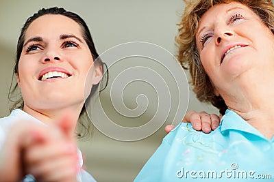 Nurse holding an elderly woman s hand