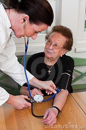 Nurse looks old woman in a nursing home