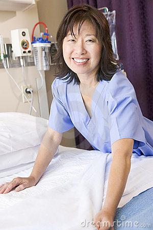 A Nurse Making A Bed Smiling