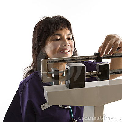 Nurse reading weight on scale.