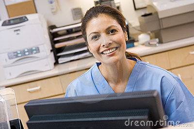 A Nurse Sitting At A Computer