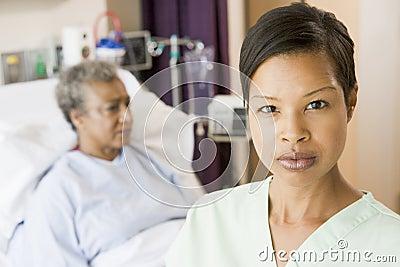 Nurse Standing In Patients Room Looking Serious