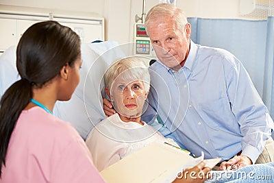 Nurse Talking To Senior Couple On Ward