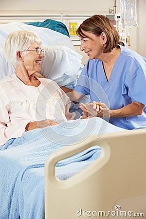 Nurse Talking To Senior Female Patient In Hospital Bed