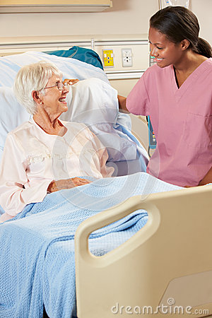 Nurse Talking To Senior Female Patient In Hospital Bed