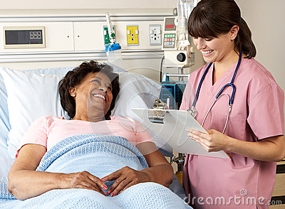 Nurse Visiting Senior Female Patient On Ward
