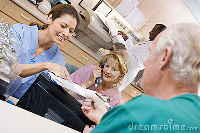 Nurses Discussing A Clipboard