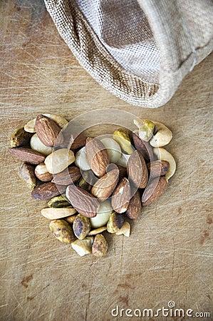Nuts in heart shape on wooden