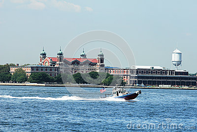 NYPD boat patrolling New York Harbor in the front of Ellis Island Editorial Image