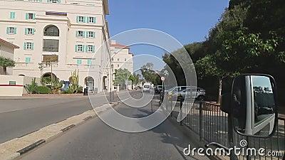 O ônibus de turista está conduzindo em ruas de Gibraltar Negociações do guia turística sobre objetos sightseeing Vista através da vídeos de arquivo
