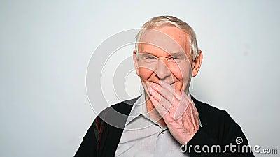 O ancião engraçado ri a boca da coberta com mão video estoque