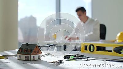 O arquiteto moreno novo senta-se pela tabela perto de uma grande janela na empresa de construção civil branca do escritório, ele  vídeos de arquivo