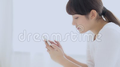O assento de sorriso da mulher asiática nova bonita do close up olhando o telefone celular esperto que lê a rede social com aprec video estoque