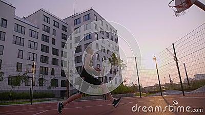 O basquetebol da prática do homem marcou a bola à aro