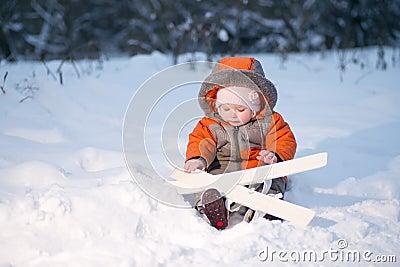 O bebê adorável senta-se na neve com esqui