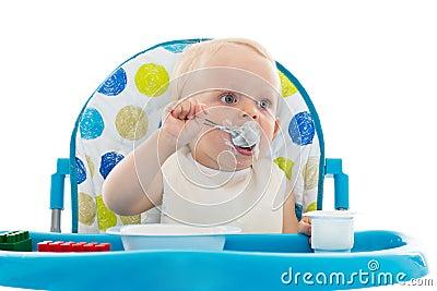 O bebê doce com colher come o iogurte.