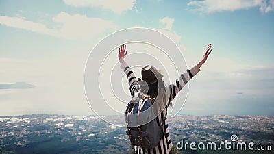 O blogger fêmea feliz do curso da vista traseira com o cabelo do voo que vem até o cenário épico da parte superior da montanha no