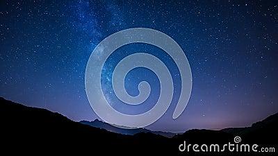 O céu noturno de Timelapse stars com Via Látea no fundo da montanha