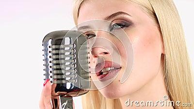 O cantor canta em um microfone retro Fundo branco Vista lateral Fim acima vídeos de arquivo