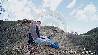 O cara que trabalha em um laptop com máscara médica longe da cidade video estoque