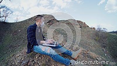 O cara que trabalha em um laptop com máscara médica longe da cidade vídeos de arquivo