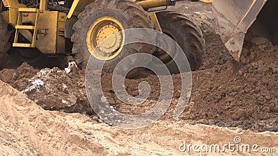 O carregador grande amarelo da construção nivela um pedaço de terra para a construção e recolhe a terra em uma cubeta, indústria, vídeos de arquivo