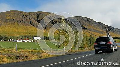 O carro está movendo-se sobre a estrada no campo em Islândia, bicicleta é fixo em um telhado, fim de semana ativo video estoque