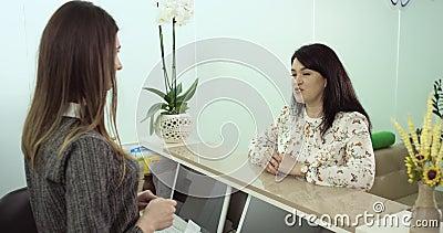 O cliente da mesa de recepção tem uma conversação com auxílio 4K video estoque