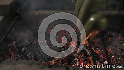 O close-up, cozinheiro chefe Inflates Coals em Mangall e vira o abobrinha cozido amarrado em espetos video estoque