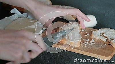 O close-up das mãos do ` s da mulher mancha a manteiga em uma parte de pão, usando uma faca Fazendo um sanduíche video estoque