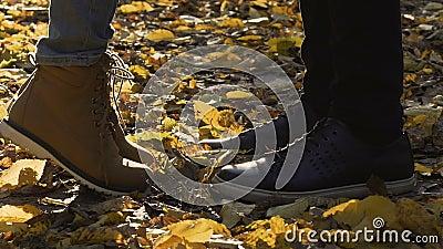 O close-up das sapatas na folha cobriu a terra, menina que alcança o noivo ao beijo, data filme