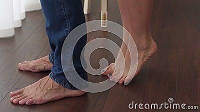 O close-up dos pés desencapados de um par de amor, a menina está em seus dedos do pé video estoque