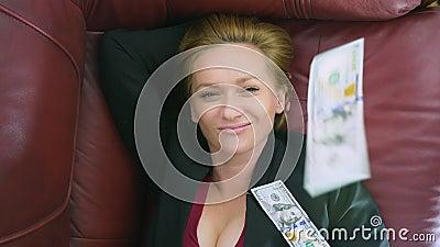 O conceito da renda passiva a mulher feliz encontra-se no sofá e nos sorrisos, sobre ela dólares de queda 4k, close-up vídeos de arquivo