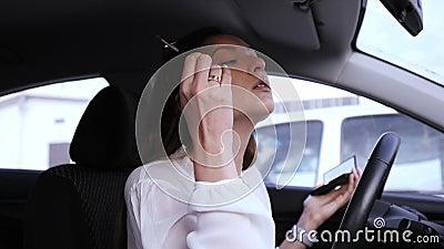 O conceito de beleza e cosmética Retrato de uma linda moça motora dentro de um carro Aplicando sombras aos olhos com vídeos de arquivo