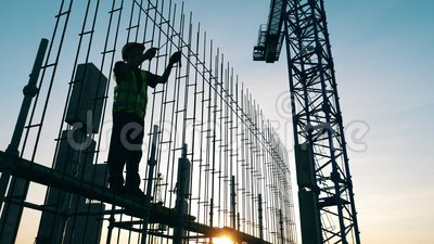O construtor está parado na carcaça da construção enquanto a monta video estoque