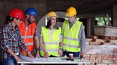 O coordenador ou o arquiteto que discutem a construção emitem com colegas video estoque