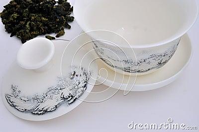 O copo de chá de cinzeladura chinês e o chá cru folheiam