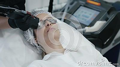 O cosmetologist ascendente próximo faz a laser a remoção vascular na cara da mulher com equipamento especial video estoque