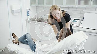 O Cosmetologist examina a cara do paciente antes do procedimento Moça na recepção no esteticista vídeos de arquivo