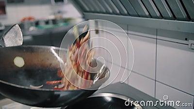 O cozinheiro chefe frita o alimento em uma bandeja do frigideira chinesa vídeos de arquivo