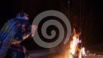 O curandeiro bate o cilindro que senta-se pelo fogo video estoque