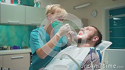 O dentista que examina os dentes pacientes do ` s, explica-o procedimento video estoque