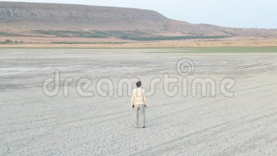 O efeito óptico da mudança de perspectivas ao usar uma lente de zoom Um homem no meio do deserto sente como o espaço é filme