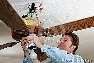 O eletricista remove o ventilador de teto