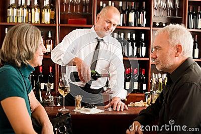 O empregado de bar sênior dos pares da barra de vinho derrama o vidro