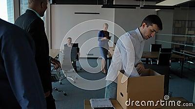 O empregado novo desembala a caixa com docs e equipamento Seus colegas que andam próximo no escritório moderno vídeos de arquivo